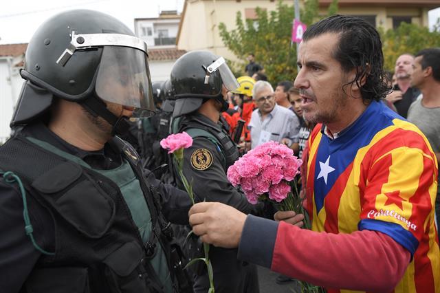 Un catalán le entrega una flor a un policía el domingo, previo a la votación