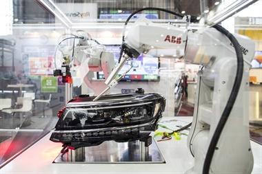 Una serie de brazos robóticos en exposición ponen a prueba los faros de un vehículo en una exposición de robots industriales en Brno, la segunda ciudad más grande de República Checa